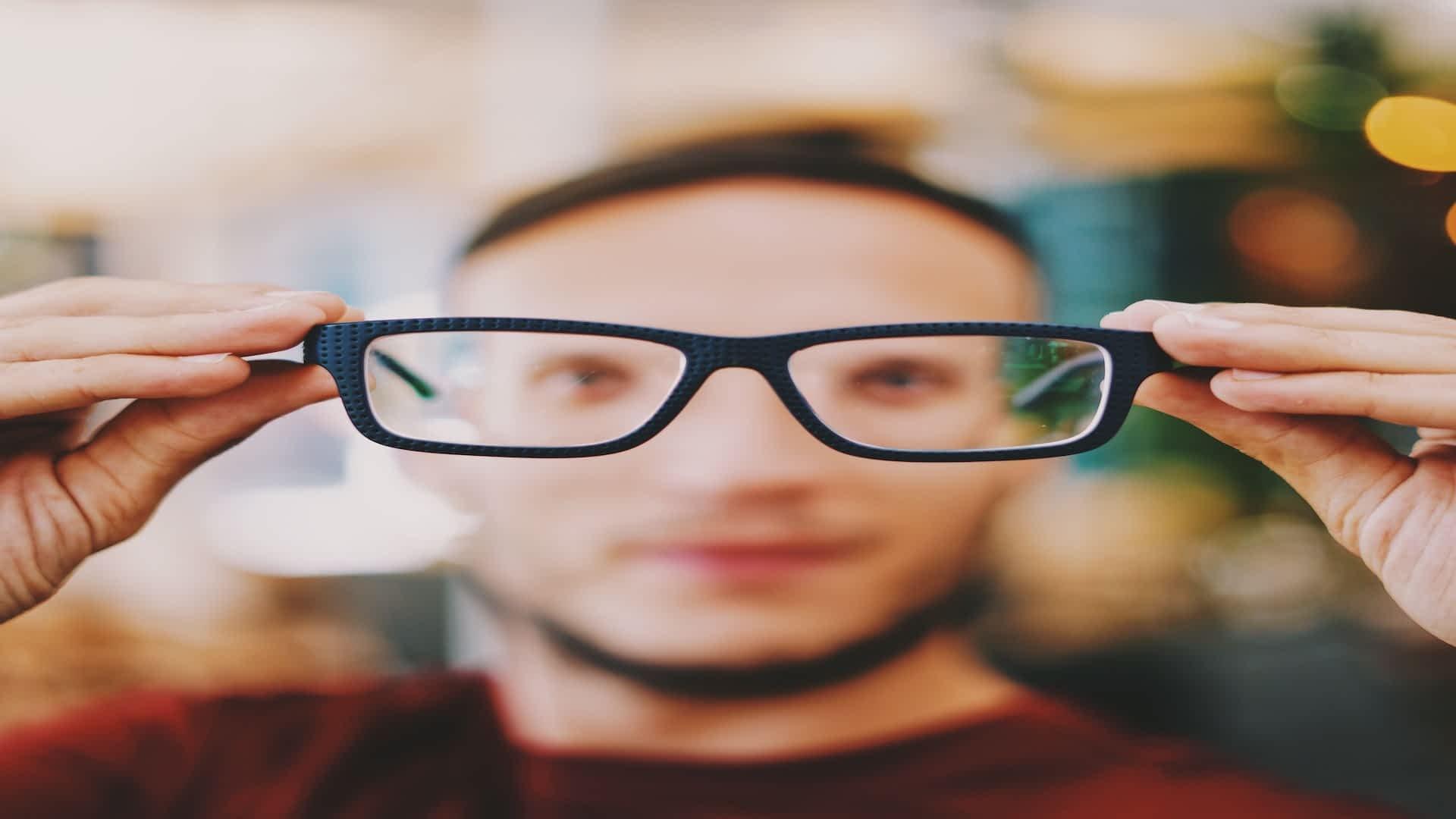 holding_up_glasses
